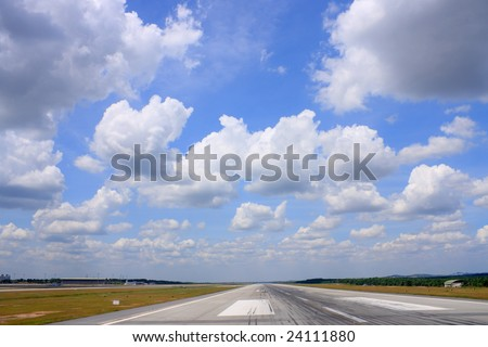 Airport runway road view under cloudy blue sky.