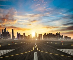 Airport runway with modern skyscrapers silhouettes on background in beautiful sunset light. Cloudy sky and sun rays. Travel and cities concept