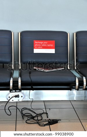 Airport seating with outlet for charging cell phones, computers - stock photo