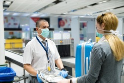 Airport security officer wears blue  gloves and mask as a healthy safety precaution to prevent COVID 19 in case of coronavirus pandemia