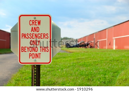 Airport Sign - Crew And Passengers Only Beyond This Point - a security  sign at a small airport at the entrance road to the plane and hangar.