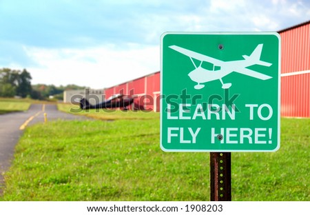 Airport Sign - Learn To Fly Here - a sign in front of the hangars at a small airport .