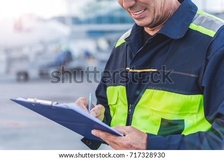 Airport technical staff hand making notes