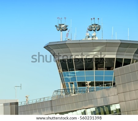 Airport terminal building facade air traffic control tower silhouette with light masts antenna red obstruction beacon lights security safety cameras against blue sky architecture theme background #560231398