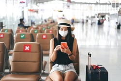 Airport terminal social distancing chair form corona virus pandemic. Young adult tourist woman sitting wear mask protect from covid 19. People travel with new normal lifestyle concept.