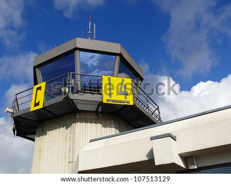 Airport traffic control tower with cloudy sky on background and strong reflection of sky in windows