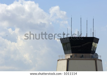 Airport traffic control tower with small airplane taking off