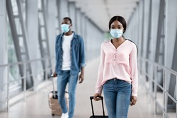 Airport Travel Precautions. Black Man And Woman Wearing Medical Masks Walking With Suitcases At Terminal, Selective Focus, Copy Space