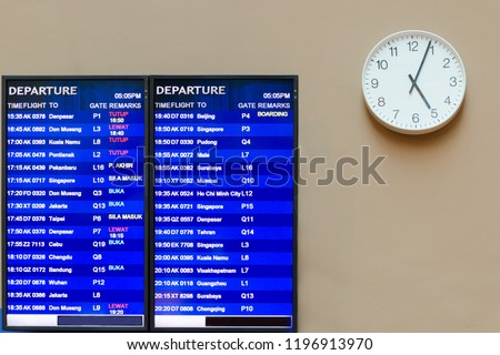 Airport wall with information board, near the clock with hands that shows four minutes past five, flight schedule. Malaysia, Kuala Lumpur, KLIA 2.