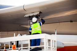 Airport worker refuelling the aircraft