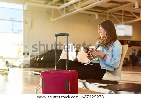 Airport Young female passenger on smart phone and laptop sitting in terminal hall while waiting for her flight