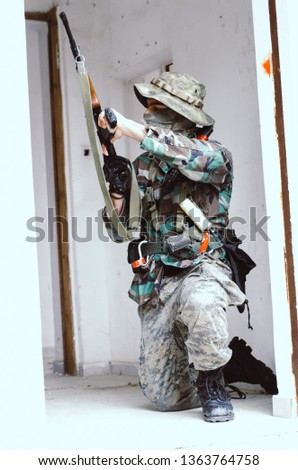 airsoft soldier reload magazine cover on wall door inside building #1363764758