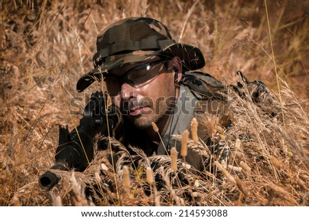 Airsoft team member in daytime action hiding in the bushes.
