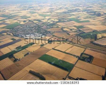 Airview of UK yellow fields of crops in  Luton, Bedfordshire, England and Greater London county. Summer 2018, heat wave, torrid fields, drought view from a plane descending at Luton airport