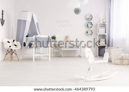 Airy baby room agganged in white and navy blue, with marine decorations #464389793