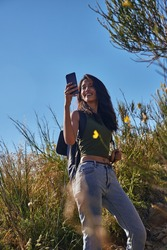 Airy young lady taking a selfie on a hill on a clear sunny day while surrounded by wild flora