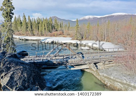 Aishihik River Bridge as seen from the Alaska Highway on a sunny day in spring.