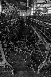 Aisle of machines at an abandoned silk mill.