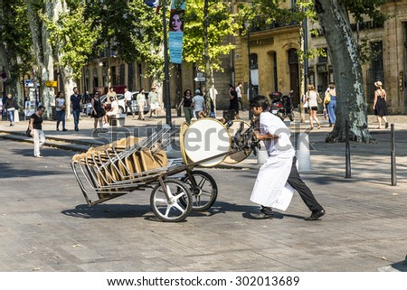 AIX EN PROVENCE, FRANCE - JULY 8, 2015: waiter carries tables for the outdoor restaurant with a sack barrow to the place. in Aix many restaurants serve outdoor dinner.