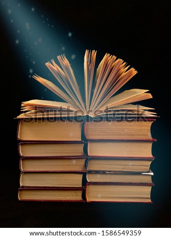 Ajar pages in the book. A stack of old hardback textbooks, on a black background. Concept: education, self-improvement, love of learning.