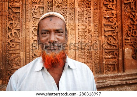 AJMER, INDIA - MARCH 06, 2013: Undefined Indian man with red beard in front of Adhai-din-ka-Jhonpra ruins in a holy Muslim city of Ajmer, India. April 06, 2013