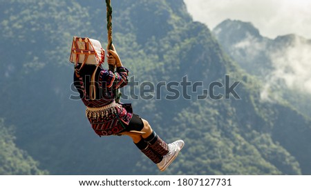 Akha girl , Hill tribe in the north of Thailand, Unidentified hill tribe was playing traditional wooden swing with traditional clothes and silver jewelry in Chiang Rai, Akha Swing Festival.