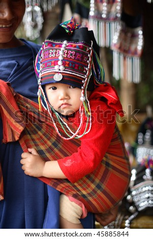 AKHA HILL TRIBE VILLAGE, THAILAND - AUG 24: Akha hill tribe woman carries a traditionally dressed child, Duo Soi, 1, August 24, 2007 in Akha hill tribe village, Thailand.