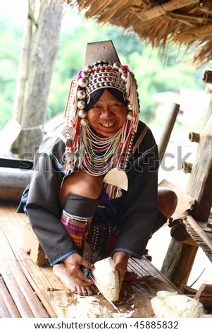 AKHA HILL TRIBE VILLAGE, THAILAND - AUG 24: Traditionally dressed Akha hill tribe woman carries out daily routine on August 24, 2007 in Akha hill tribe village, Thailand.