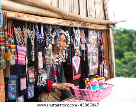 AKHA HILL TRIBE VILLAGE, THAILAND - AUG 24: Traditionally dressed Akha hill tribe woman sells goods at the local market on August 24, 2007 in Akha hill tribe village, Thailand.