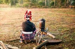 Akha tribe women cooking with traditional stoves outdoors on the mountains in northern Thailand. Lifestyle of hill tribal cooking in the morning at her house, hill tribe village. Thailand - CHIANG Rai