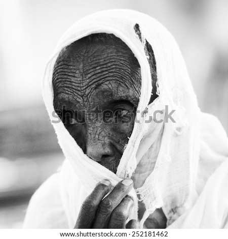 AKSUM, ETHIOPIA - SEP 24, 2011: Unidentified Ethiopian old woman wearing white tissue in Ethiopia, Sep.24, 2011. People in Ethiopia suffer of poverty due to the unstable situation