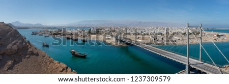 Al Ayjah Bridge in Sur, Oman. The bay is dotted with traditional wooden dhow boats, while the whitewashed town can be seen in the background