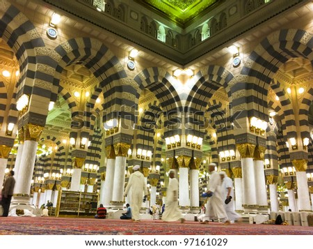AL MADINAH, KINGDOM OF SAUDI ARABIA-FEB. 19: Muslim men walk on inside Masjid (mosque) Nabawi on February 19, 2012 in Al Madinah, S. Arabia. Nabawi mosque is the 2nd holiest mosque in Islam.
