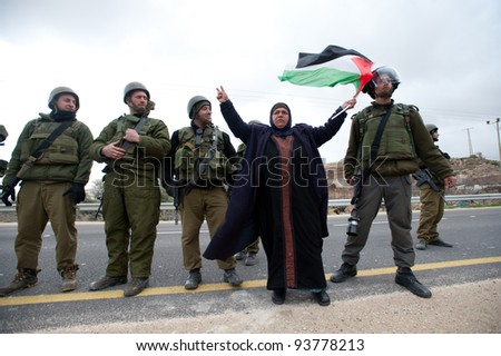 AL-MASARA, PALESTINIAN TERRITORIES - JANUARY 27: A Palestinian woman waves a flag while confronting soldiers in a protest against the Israeli separation wall in Al-Masara, West Bank on Jan 27, 2012.