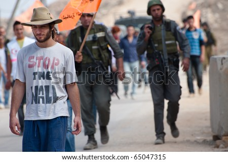 "AL-WALAJA, - NOVEMBER 13: An Israeli activist in a ""Stop the Wall"" shirt marches on Nov. 13, 2010 to protest the Israeli separation wall in Al-Walaja."