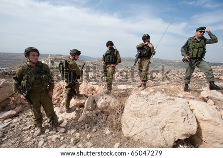 AL-WALAJA - NOVEMBER 13: Israeli soldiers stand by during a nonviolent protest against the Israeli separation barrier on Nov. 13, 2010 in Al-Walaja. - Shutterstock ID 65047279