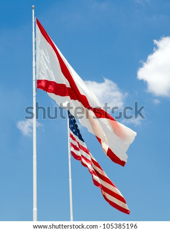 Alabama state flag and U.S. flag together under cloudy blue sky