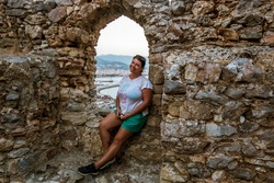 Alania.Turkey.September 4, 2020.A girl sits on the wall of the medieval fortress of Alanya in Turkey at sunset