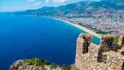 Alanya beach top view on the mountain with coast ferry boat on blue sea and harbor city background / Beautiful cleopatra beach Alanya Turkey landscape travel landmark
