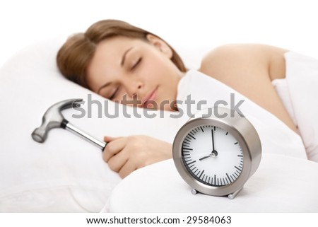 Alarm clock against the sleeping girl with a hammer in a hand