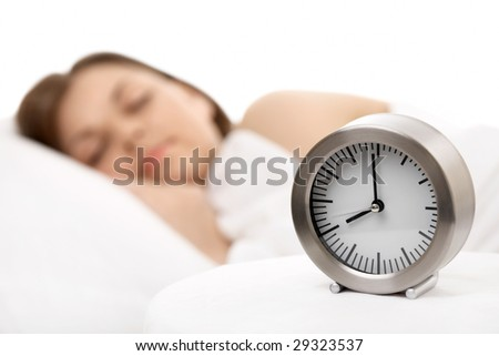 Alarm clock against the sleeping woman, horizontally