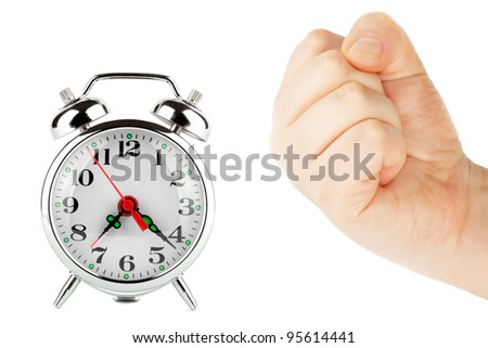 Alarm clock and a fist on the white background - stock photo