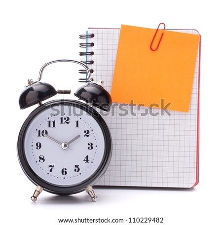 Alarm clock and  blank notebook sheet. Schoolchild and student studies accessories. Back to school concept.