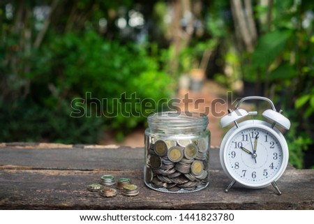 Alarm clock and coin in glass with garden background, finance and business concept, copy space