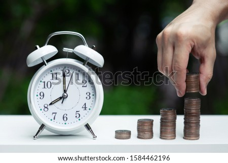 Alarm clock and coin piles arrange into growth chart on white background, finance and business concept, copy space