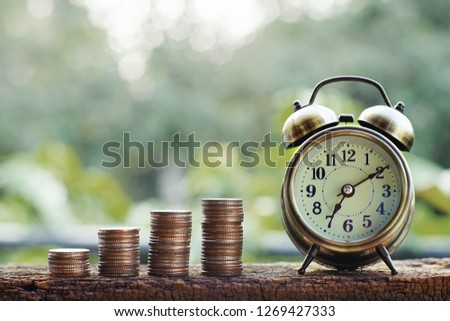 Alarm clock and coin stacks on wooden table with blur green garden background, bright morning color tone, finance and business concept, copy space