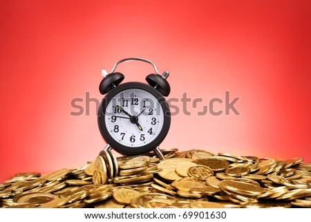Alarm clock and coins on red background