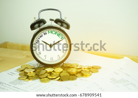 Alarm clock and coins with text time is gold. Finance concept. Time is a valuable resource, therefore it is better to do things as quickly as possible #678909541
