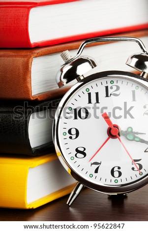 Alarm clock and colourful books extreme closeup