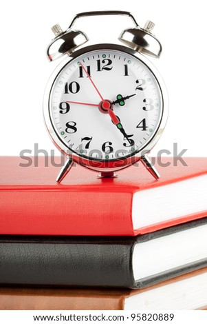 Alarm clock and colourful books extreme closeup
